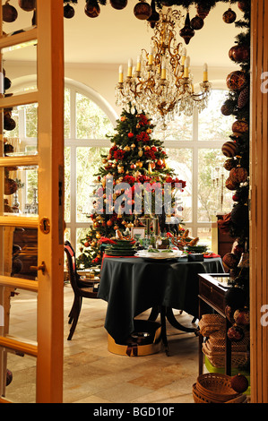 View into a conservatory with a decorative table setting in front of a decorated Christmas tree for sale, Villa - Stock Photo