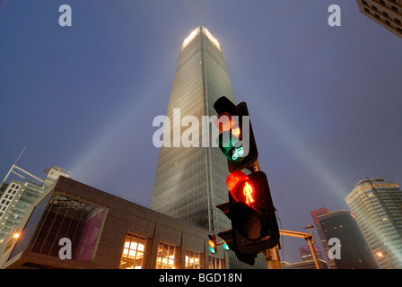 Red yellow green traffic light at the blue hour in front of a modern skyscraper, in Beijing, Guomao District, Beijing, - Stock Photo
