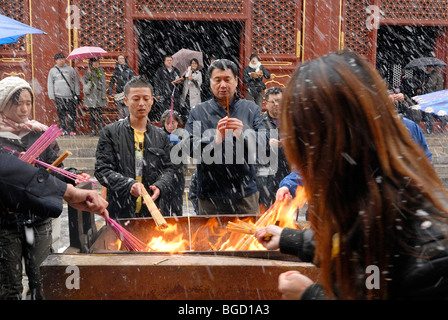 Chinese men and women lighting incense on an open fire to during heavy snowfall, snowy Buddhist Lama Temple in the - Stock Photo