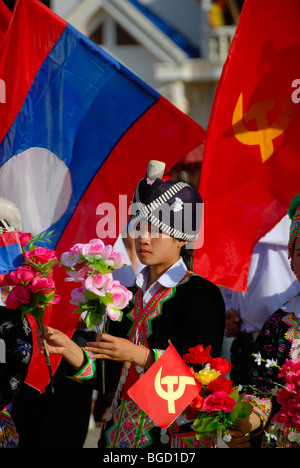 Festival, Hmong girl, dressed in traditional clothing, holding red flags of the Communist Party, national flag of Laos, Xam Neu