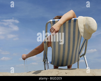 Woman relaxing on the beach on deckchair playing with sand - Stock Photo