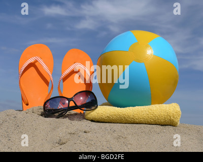 Orange flip-flops driven vertically into beach sand, sunglasses, inflated beach ball and  yellow bath towel over - Stock Photo