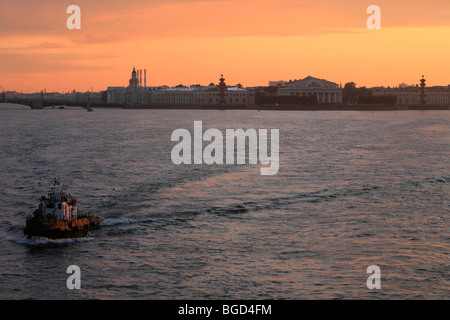 Tugboat on the Neva River with the Central Naval Museum in the background in Saint Petersburg, Russia - Stock Photo