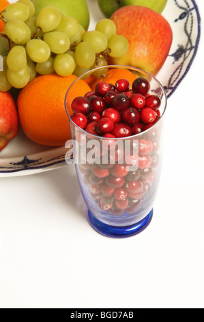 Raw cranberries in a glass next to a plate of mixed fruit - Stock Photo