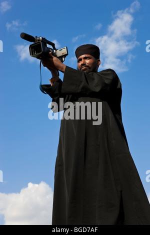 Priest with video camera, Timket (celebration of Epithany, Christian Orthodox Church) Addis Ababa, Ethiopia - Stock Photo