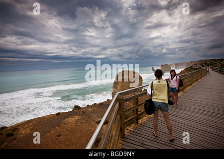 Young tourists photographing each other on board walk at the Twelve Apostles. South West Victoria, Australia. - Stock Photo