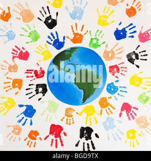 Multicoloured painted children's hand prints around the world - Stock Photo