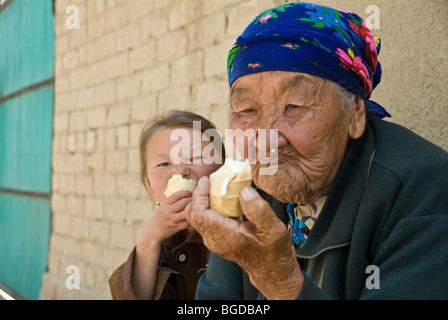 Old woman eating Ice cream in the street. Bokonbayebo, Kyrgyzstan - Stock Photo