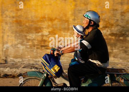 Vietnamese father with his son on his motor scooter with a backpack, Hoi An, Vietnam, Southeast Asia - Stock Photo