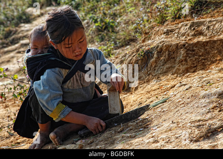 Small child with a baby on her back, sitting on a trail in the mountains of North Vietnam near the mountain town - Stock Photo