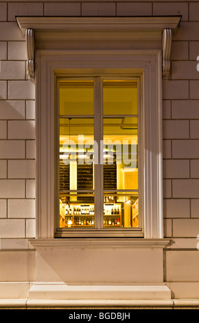 View into the illuminated window of a bar - Stock Photo