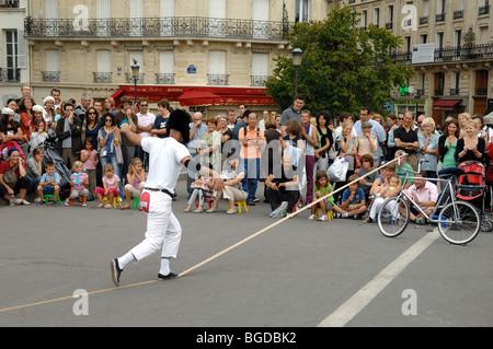 Street Theatre or Street Entertainer Balancing on Imaginary Tightrope, Pont Saint Louis, Île Saint Louis, Paris, - Stock Photo