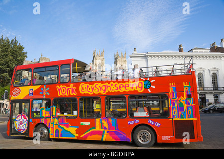 York CitySightseeing, tourist bus, against medieval York with York Minster in the back, Yorkshire, England, United - Stock Photo