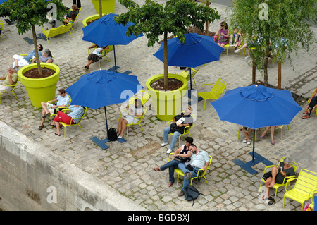 People Relaxing, Blue Parasols & Deckchairs Along Quai of the River Seine during 'Paris-Plage' Events, Paris, France - Stock Photo