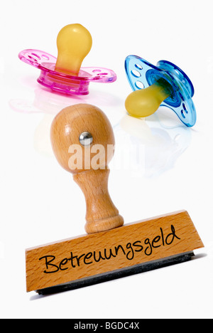 Pacifier and stamp with the word Betreuungsgeld, child care cash benefit - Stock Photo