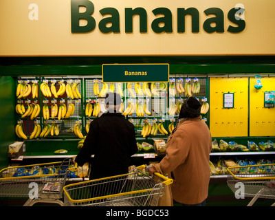 Shoppers Buying Bananas in a Supermarket - Stock Photo