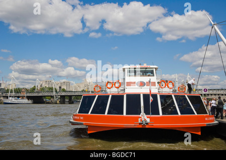 City Cruises boat on river Thames against Hungerford Bridge with the Golden Jubilee Walkways, view from river Thames, - Stock Photo