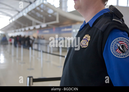 Romulus, Michigan - A security officer watches passengers arriving at Detroit Metropolitan Airport. - Stock Photo