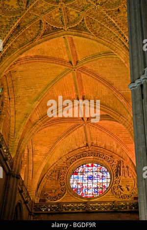 Stained Glass window and ceiling above the Door of the Prince (or of San Cristobal) at the Seville Cathedral and - Stock Photo
