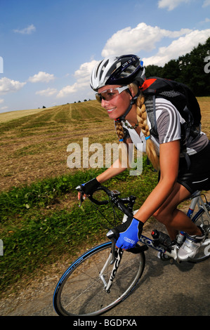 Young woman riding a bicycle, Bavaria, Germany, Europe - Stock Photo