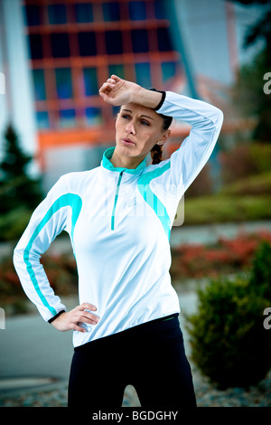 Young woman taking a break while jogging - Stock Photo