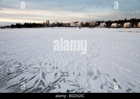 People walking on frozen lake. Tjornin lake, downtown Reykjavik, Iceland. - Stock Photo