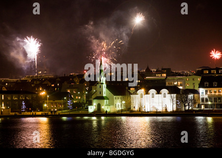 New years eve fireworks at midnight. Downtown Reykjavik, Iceland. Frikirkjan church (C) and The National Gallery - Stock Photo