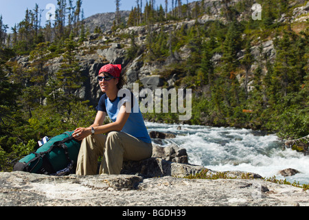 Young woman, hiker, backpacker sitting on rock, resting, Moose Creek Canyon, waterfall behind, historic Chilkoot - Stock Photo