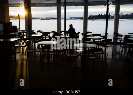 Person watching the late midday sunrise in a cafe. Reykjavik City Hall, Iceland. - Stock Photo