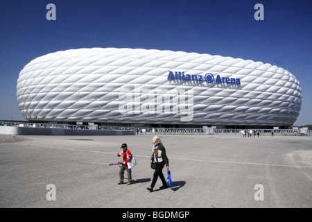 Football fans walk outside of the Allianz Arena in Munich, Germany. - Stock Photo