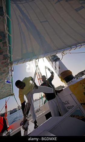ASWAN, EGYPT. Nubian crew sailing a felucca on the Nile. 2009. - Stock Photo