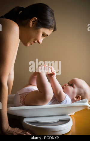 Mother weighing baby - Stock Photo
