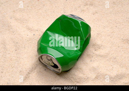 A green tin can tossed as trash on a sand beach - Stock Photo