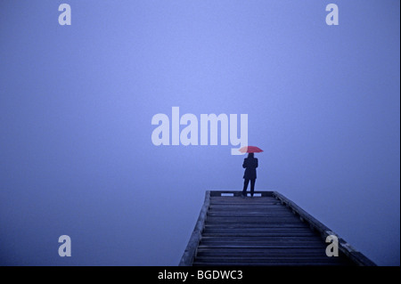 Lake Washington at sunrise in fog with single woman on a long dock holding a red umbrella - Stock Photo