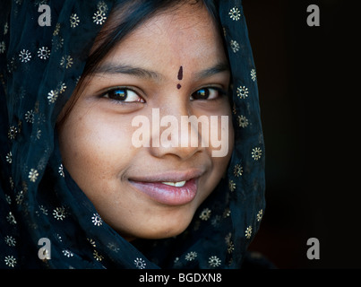 Smiling happy Indian girl wearing a black shawl. Andhra Pradesh, India - Stock Photo