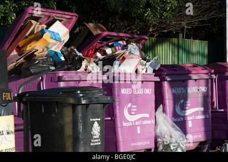 Overflowing recycling bins filled with the wrong rubbish.  Bins marked mixed glass only are filled with cardboard - Stock Photo