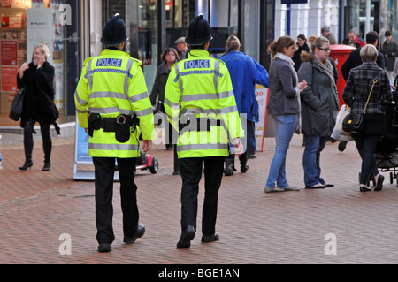 Two policemen on patrol in busy shopping high street - Stock Photo