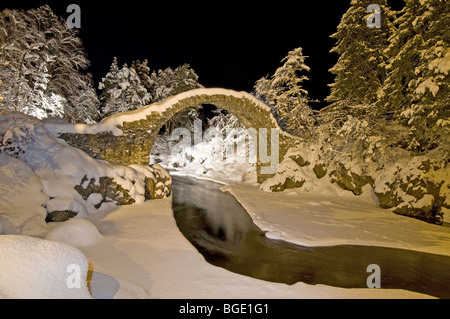 The Packhorse Bridge at Carrbridge Floodlit in Winter Snow Strathspey Inverness-shire Highland Scotland.  SCO 5724 - Stock Photo
