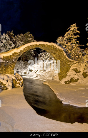 The Packhorse Bridge at Carrbridge Floodlit in Winter Snow Strathspey Inverness-shire Highland Scotland.  SCO 5729 - Stock Photo