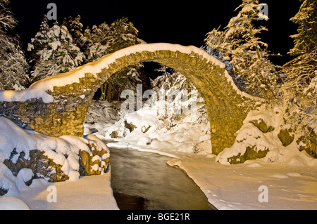 The Packhorse Bridge at Carrbridge Floodlit in Winter Snow Strathspey Inverness-shire Highland Scotland.  SCO 5723 - Stock Photo