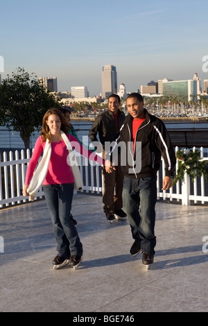 Multi-ethnic group of friends ice skating on a synthetic ice rink aboard the Queen Mary Hotel and Attraction in - Stock Photo