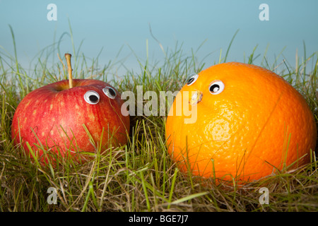 Apple and orange fruit with smiley eyes in green grass - Stock Photo