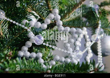White star and bead decorations on a real Christmas tree. - Stock Photo