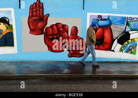 Man walks past new murals, painted at the start of 2010 on the loyalist end of Northumberland Street, Shankill Road, - Stock Photo