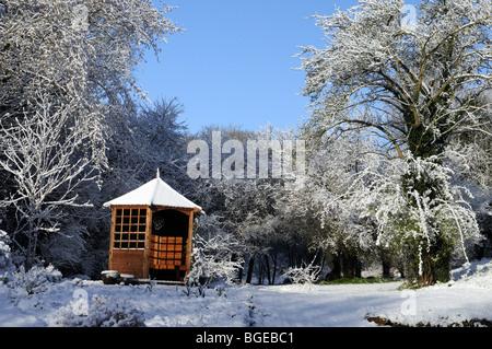Gazebo in Shropshire garden in winter snow - Stock Photo