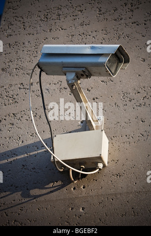 A security camera, photographed against the concrete wall it's mounted on. - Stock Photo