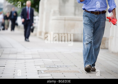Commuters in business and casual clothes walk to work over Waterloo Bridge, London, England. No recognisable faces - Stock Photo