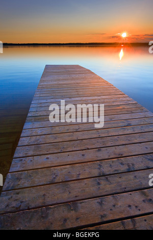 Sunset over a wooden wharf at Lake Audy, Riding Mountain National Park, Manitoba, Canada. - Stock Photo
