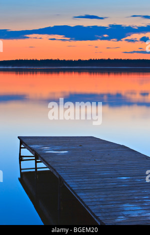 Sunset over a wooden wharf on Lake Audy, Riding Mountain National Park, Manitoba, Canada. - Stock Photo