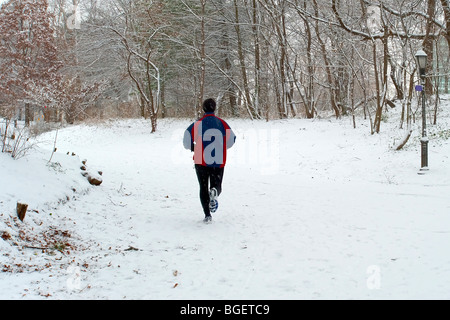 A lone jogger makes his way along a snowy trail in Prospect Park, Brooklyn, NY - Stock Photo